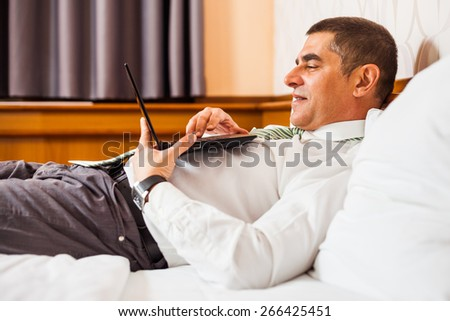 Businessman lying in bed and surfing the net on laptop