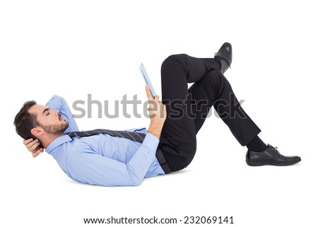 Businessman lying on floor using tablet on white background - stock photo