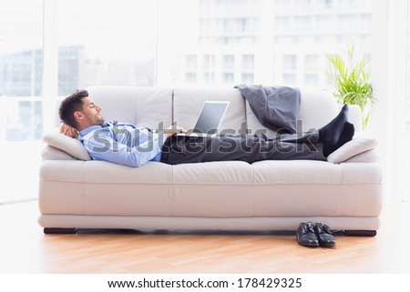 Businessman lying on sofa using his laptop in the office - stock photo