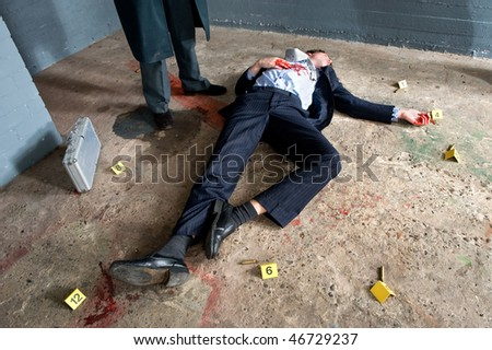 Businessman lying on the concrete floor of a basement, being shot, surrounded by evidence placards, and a man wearing a long overcoat hovering over the body - stock photo
