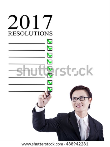 Businessman make a list of his resolutions in 2017, shot in studio isolated on white