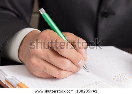 Businessman makes notes to his work diary - stock photo