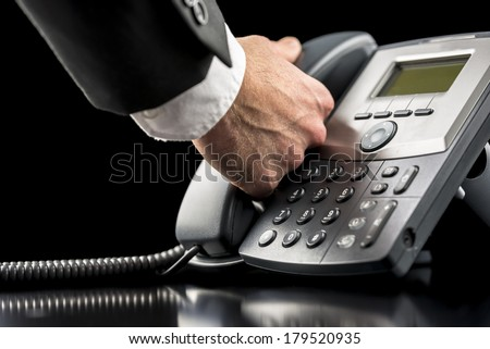 Businessman making a call on a landline telephone lifting the handset from the desktop instrument as he prepares to dial the number, closeup of his hand and the telephone in a communications concept. - stock photo
