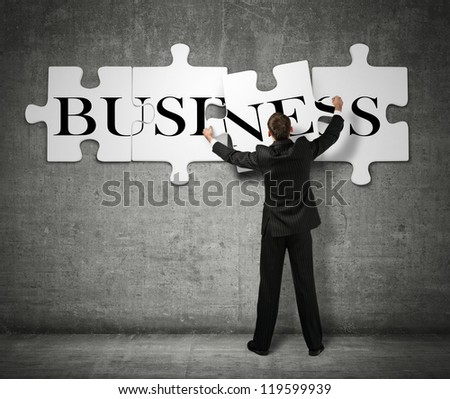 Businessman making a puzzle on the wall with the word Business - stock photo