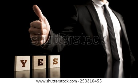 Businessman making a thumbs up gesture over a Yes sign. Conceptual of great success and personal satisfaction. - stock photo