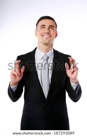 Businessman making a wish and looking up over gray background