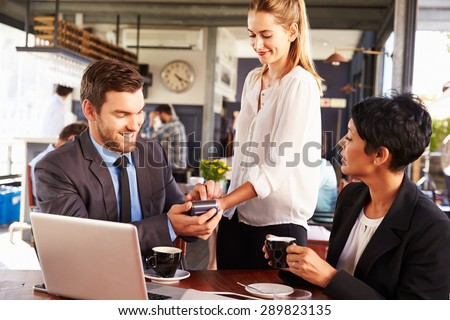 Businessman making credit card payment in a cafe - stock photo