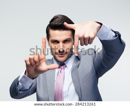 Businessman making frame gesture over gray background and looking at camera - stock photo