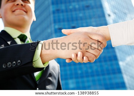 Businessman making handshake with partner over office building - stock photo