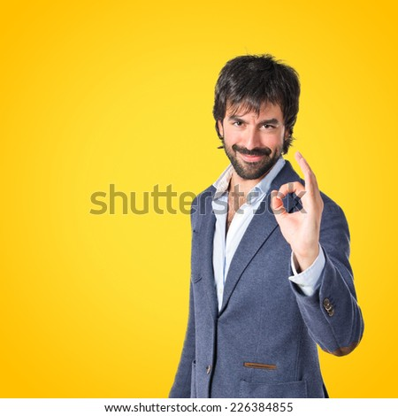 Businessman making Ok sign over yellow background