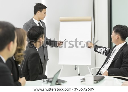 Businessman making presentation in bright office with a blank board for copyspace