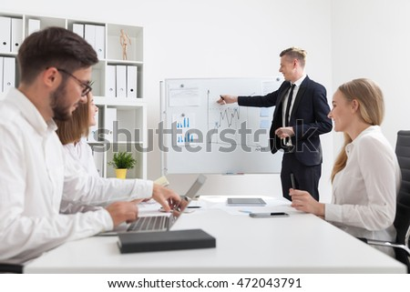 Businessman making presentation in meeting room. His coworkers listening and asking questions. Concept of business process.