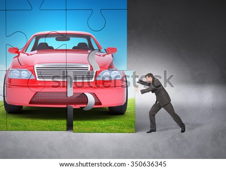 Businessman making puzzle with picture of car - stock photo