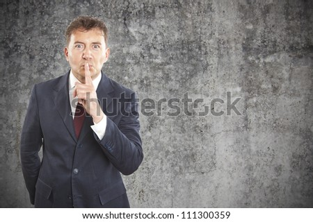 businessman making silence gesture on cement background - stock photo