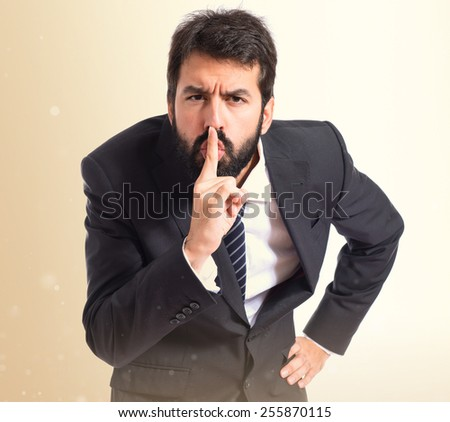 Businessman making silence gesture over ocher background - stock photo