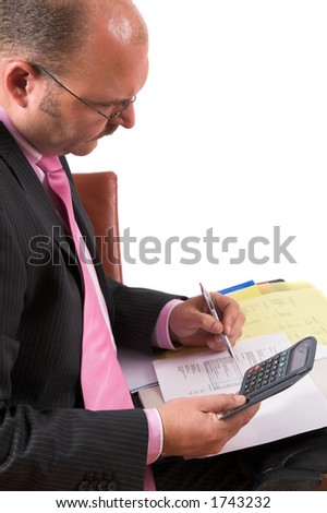 Businessman making some calculations on his calculator - stock photo