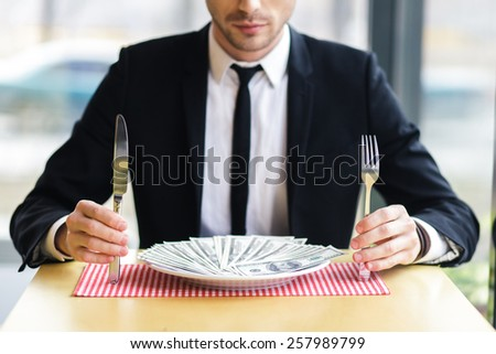 businessman male eating his money, concept. eats dollars. handsome businessman makes a lot of money - stock photo