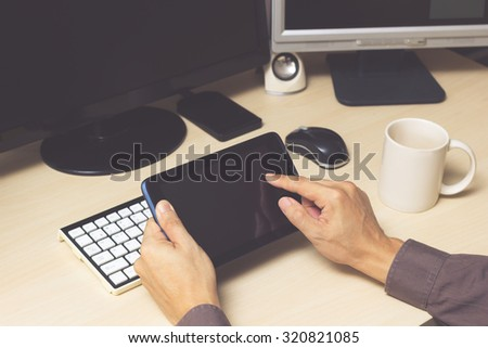 businessman, male employee hands with tablet computer on workspace desk in office - stock photo