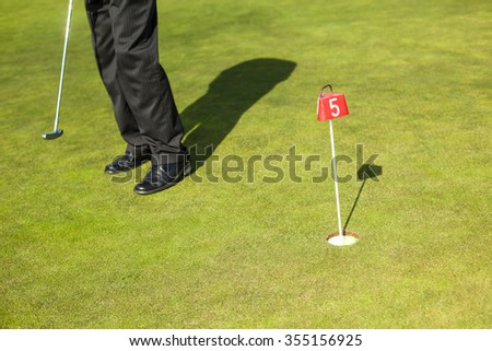 Businessman man playing golf on golf course
