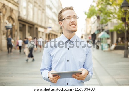 Businessman Man Using Tablet Computer in public space, street, city - stock photo