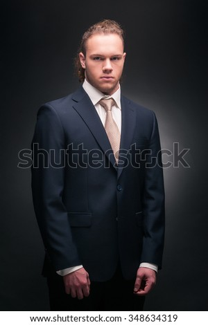 Businessman, man with long hair in black suit on a dark background, a businessman in a black suit on a dark background