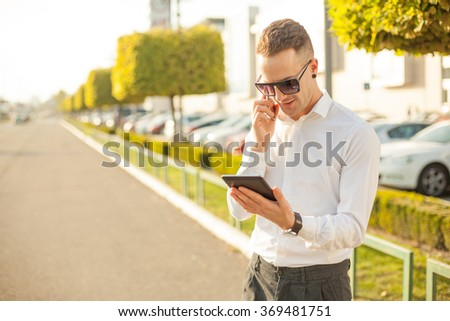 Businessman Man With Mobile Phone and Tablet computer in hands, In City, Urban Space