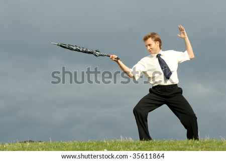 businessman man with umbrella fencing in a park - stock photo