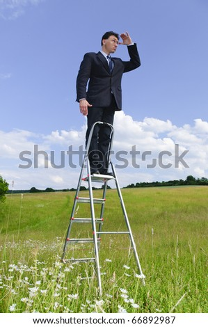 Businessman, manager in a suit, standing outside on a lawn outside the corporate ladder in front of clouds - stock photo