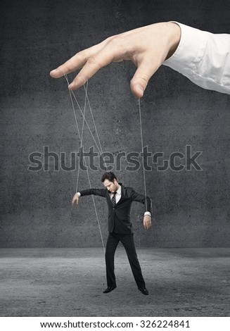 Businessman marionette on ropes controlled  hand - stock photo