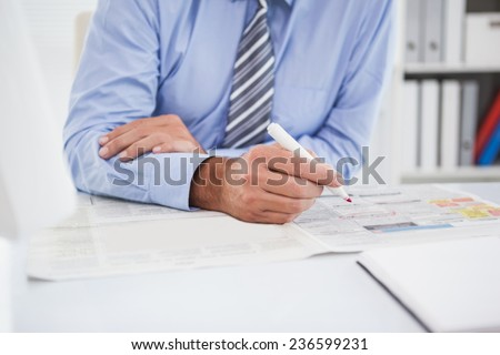 Businessman marking the newspaper with marker in his office