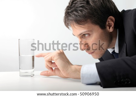 Businessman measuring water in a glass - stock photo