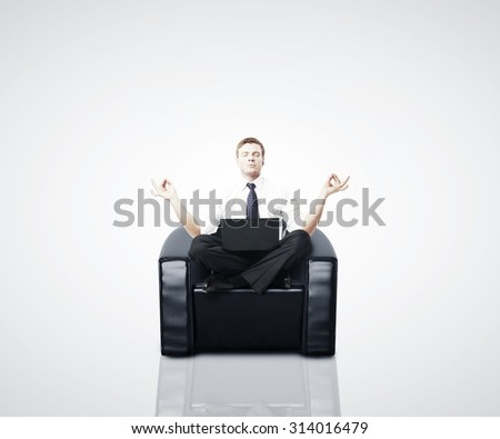 businessman meditating in a chair with a laptop - stock photo