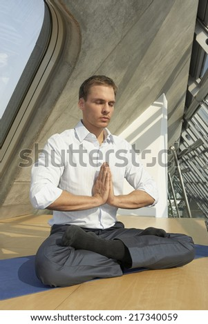 Businessman meditating in an office - stock photo
