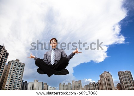Businessman meditating in the air before modern building