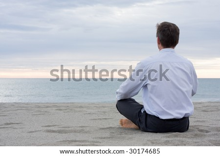 Businessman meditating on a beach at the sea - stock photo