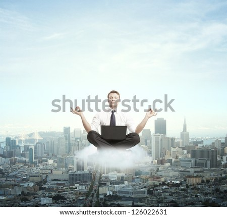 businessman meditating on a cloud - stock photo