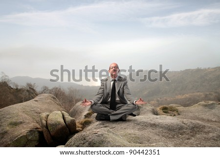 Businessman meditating on a rock in the mountains - stock photo
