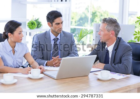 Businessman meeting with colleagues using laptop in the office - stock photo