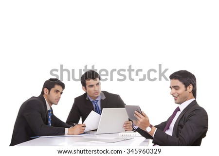 Businessman messaging as colleagues watch on