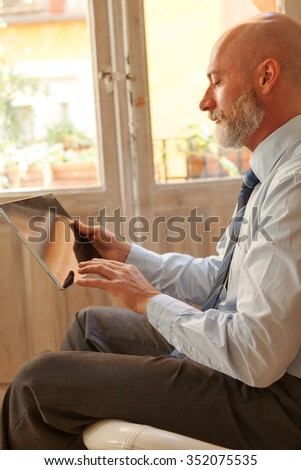 Businessman middle-aged bearded and suit jacket searching on tablet on a blurred background - stock photo