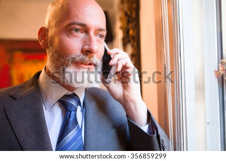 Businessman middle-aged bearded and suit jacket talking on smartphone on a blurred background - stock photo