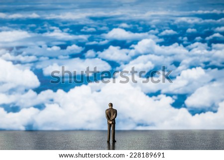 businessman miniature look at blue sky - stock photo