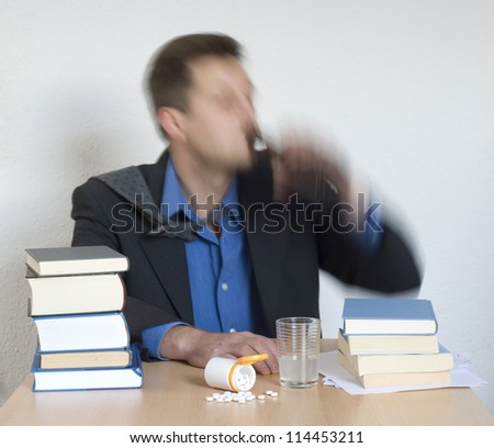 Businessman mixing pills and alcohol in the office.