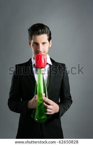 Businessman modern valentine plastic rose flower in hand over gray background - stock photo