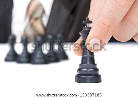 Businessman moves chess king figure with pawn team behind - stock photo