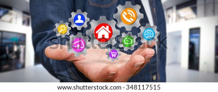 Businessman moving digital gears with his hand in his office