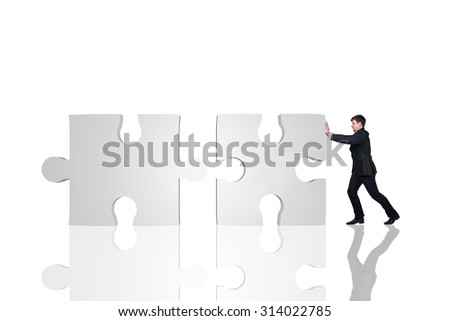 Businessman moving puzzle  on the white background - stock photo