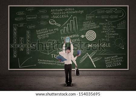 Businessman multitasking with business doodle writings on blackboard - stock photo