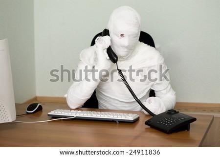Businessman mummy talking on telephone on white - stock photo