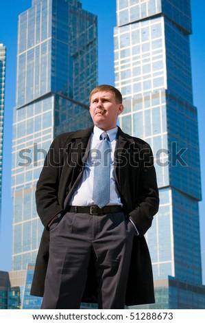 Businessman near skyscrapers - stock photo